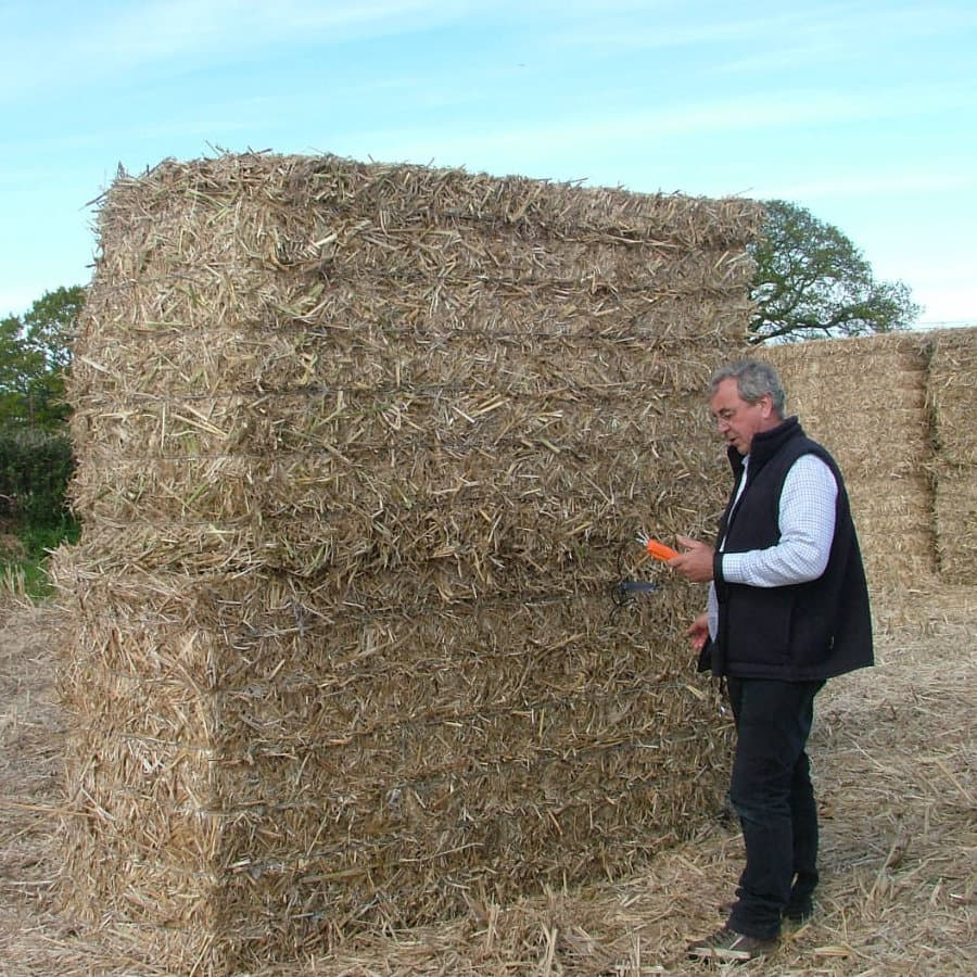 Mike Cooper (Managing Director) out in the field checking the moisture content of the bales before being moved to storage.